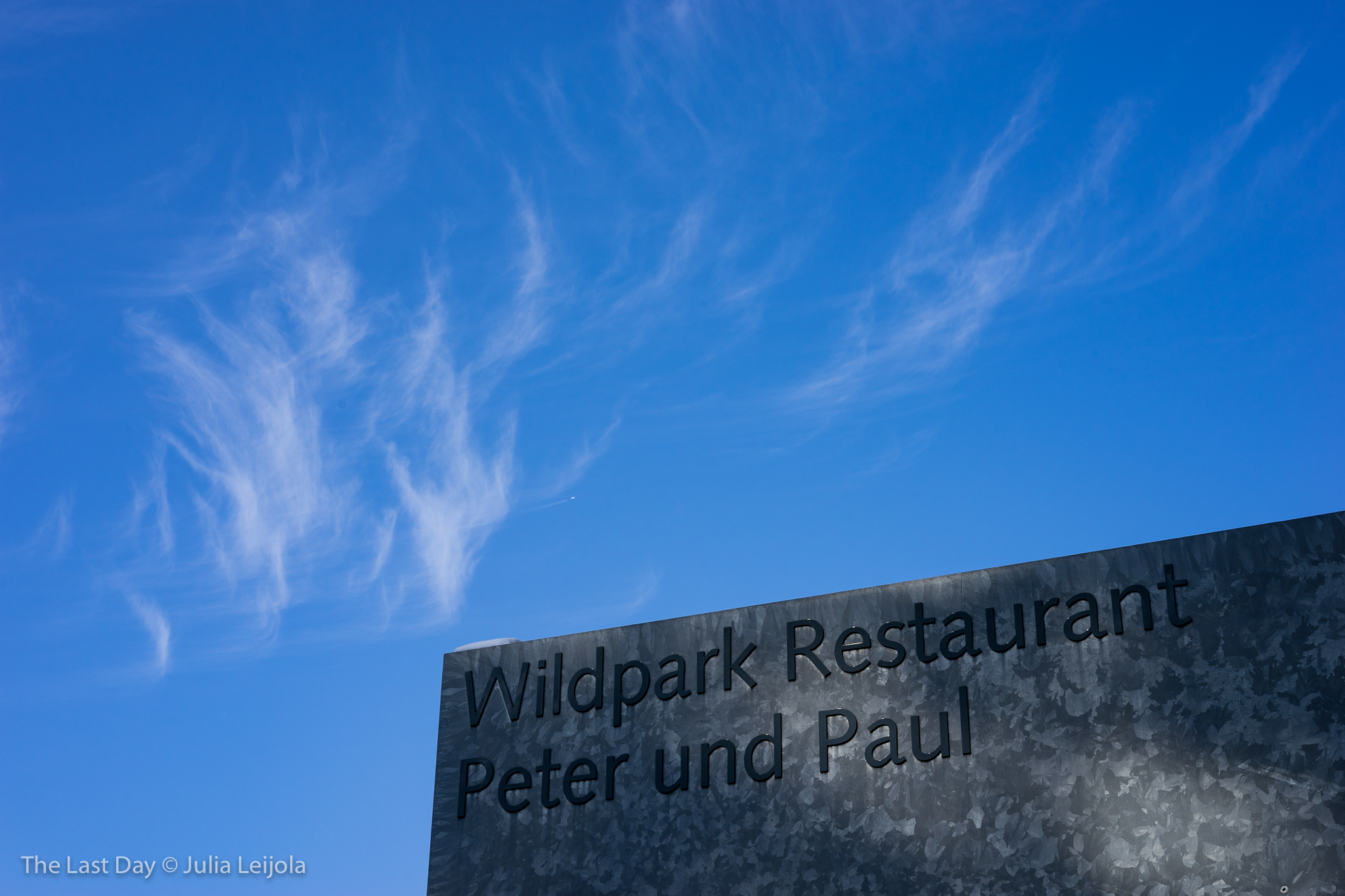 Corner of the Wildpark Restaurant and a bright blue sky with cirrus clouds and an airplane high in the sky.
